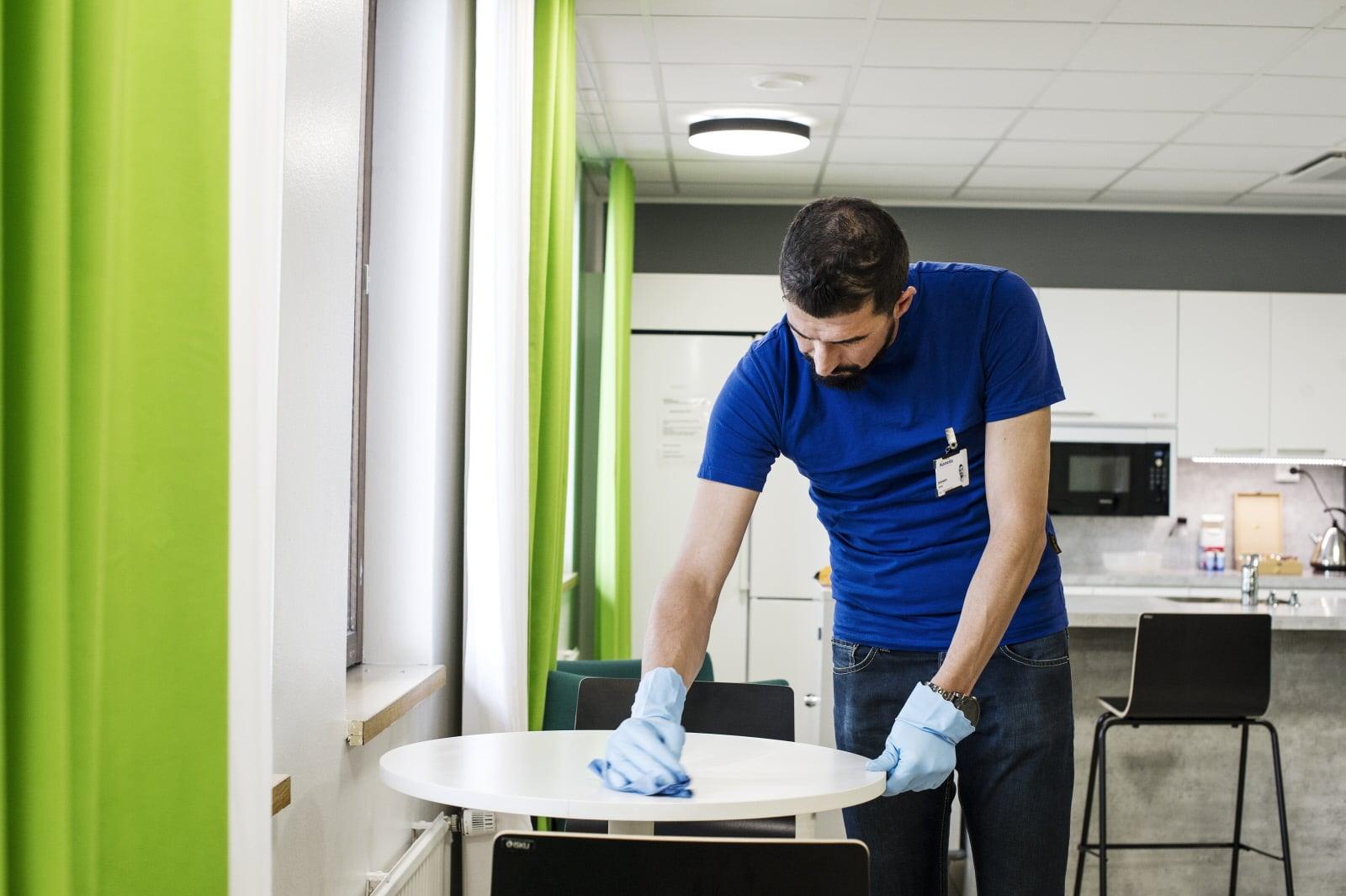 Siivooja puhdistamassa pöytää